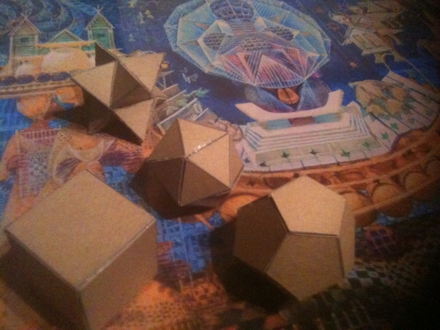 Four out of five platonic solids on top of a John Biggers reproduction.