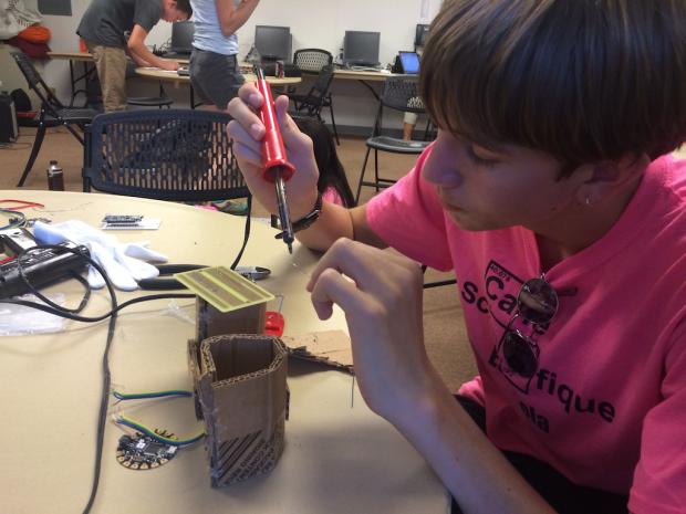 Emmett solders a prototype breadboard.