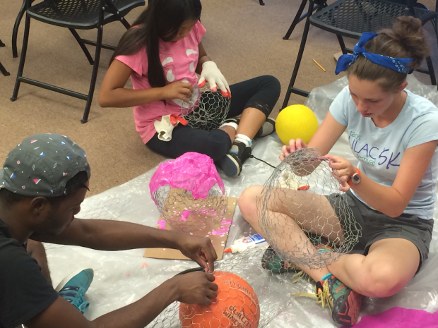 Hailey, Justis and Kyonna use chicken wire and tissue papier-mâché to make colored rocks.